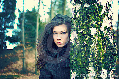 Young woman hiding behind birch tree