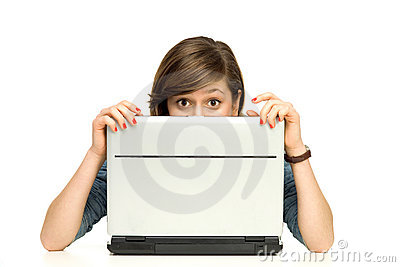 Young woman hiding behind a laptop