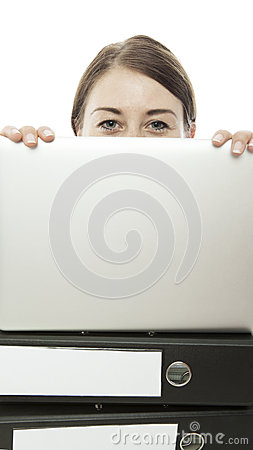 Young woman is hiding behind laptop and documents