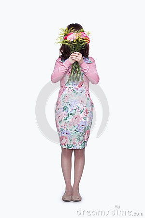 Young woman hiding face behind bouquet of flowers