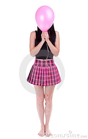 Young woman hiding her face behind pink balloon