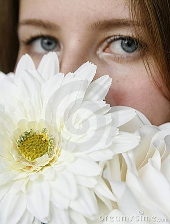Young woman hiding her face with white flowers