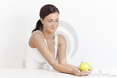 Young woman holding apple over white smiling