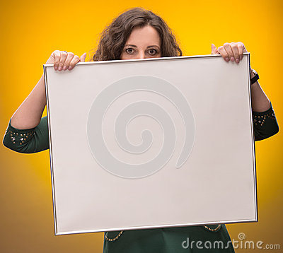Young woman holding empty billboard