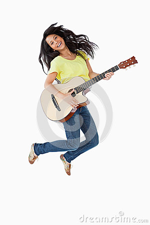 Young woman holding a guitar while jumping