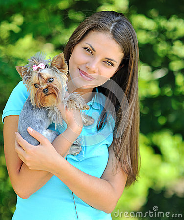 Young woman holding her sweet little puppy - outdoor portrait
