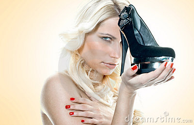 Young woman holding high heels shoe