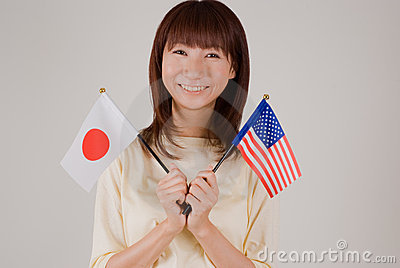 Young woman holding Japanese and American flags