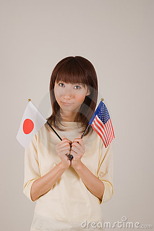 Young woman holding Japanese flag and American fla