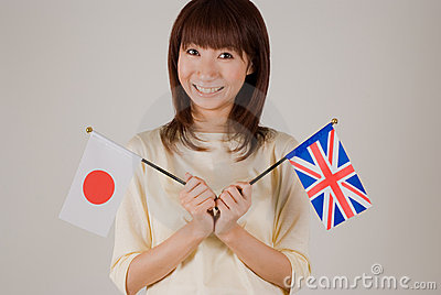Young woman holding Japanese flag and British flag