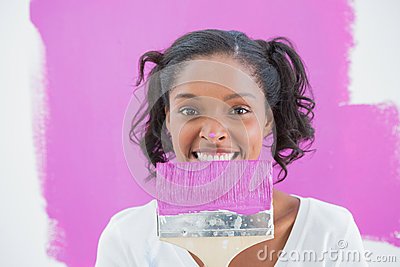 Young woman holding paintbrush with paint on her nose