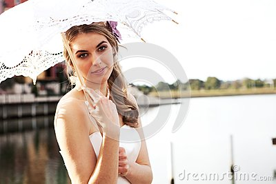 Young Woman Holding a Parasol by the Water