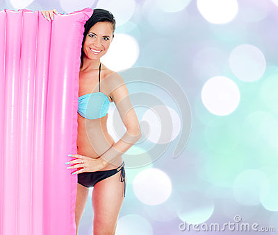 Young woman holding pink inflatable mattress