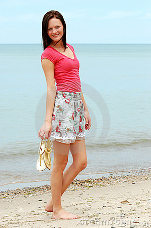 Young woman holding sandals on the beach