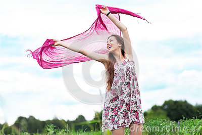 Young woman holding scarf to wind