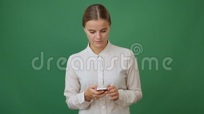 Young woman holding a smartphone and making a call. Green screen background stock video