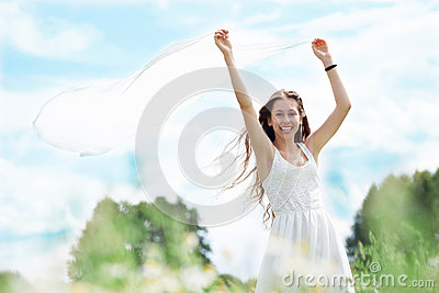 Young woman holding white scarf to wind