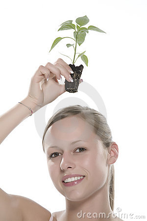Young woman holding young sprout in the hands.