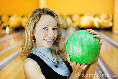 Young woman holds ball in bowling club