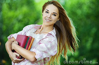 Young woman holds lot books