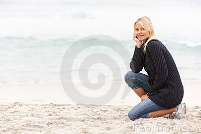 Young Woman On Holiday Kneeling On Beach