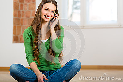 Young woman at home on the phone
