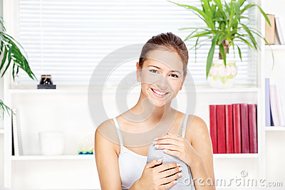 Young woman at home sitting on the sofa