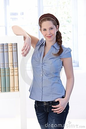 Young woman at home standing by bookshelf