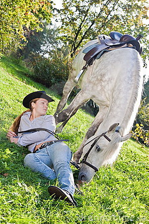 Young woman with a horse on the field