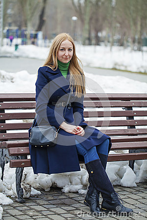 Free Young Woman In A Blue Coat Sitting On A Bench In Winter Park Royalty Free Stock Photography - 71001727