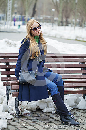 Free Young Woman In A Blue Coat Sitting On A Bench In Winter Park Stock Photos - 71003533