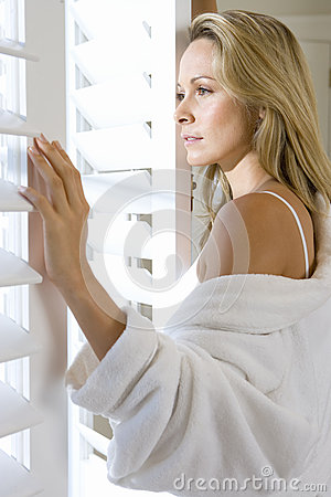 Free Young Woman In Bathrobe Looking Out Window With Shutters, Close-up, Side View Stock Photography - 41709632