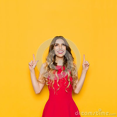 Free Young Woman In Red Dress Is Smiling, Pointing And Looking Up. Stock Photography - 115933562