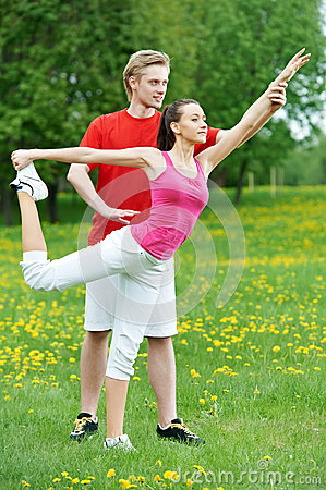 Young woman and instructor doing exercises