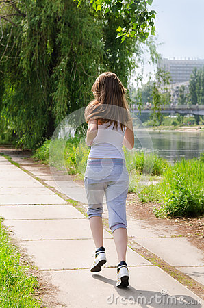 Young woman jogging alongside a river