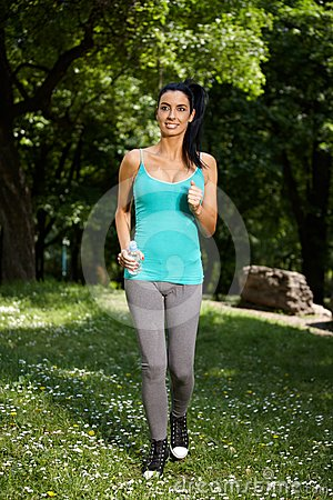 Young woman jogging in nature smiling