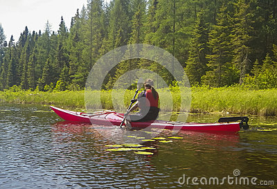 Young woman in kayak on a pond