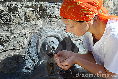 Young woman in kerchief drinking water