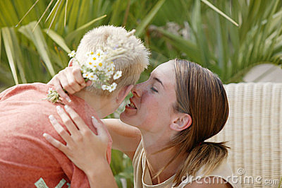 Young woman kissing little boy