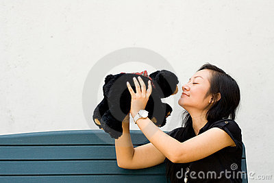 Young woman kissing teddy bear