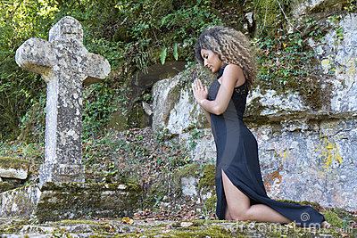 Young woman kneeling to pray