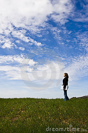 Young woman with laptop in meadow