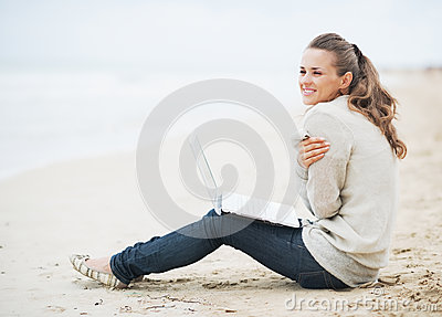 Young woman with laptop sitting on beach