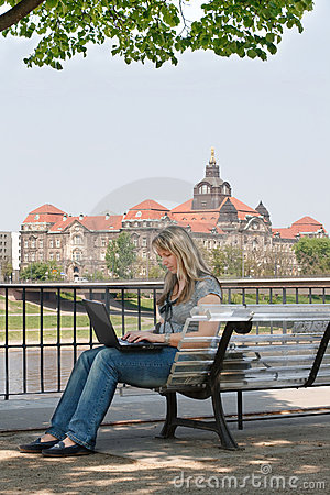 Young woman with laptop sitting on the bench.