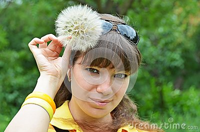 Young woman with large dandelion