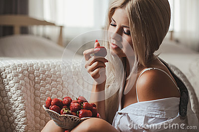Young woman laying on bed with strawberry