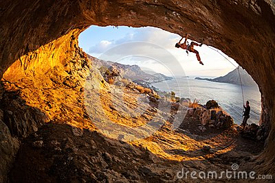 Young woman lead climbing in cave Stock Photo