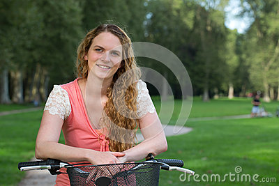 Young woman leaning against a bike