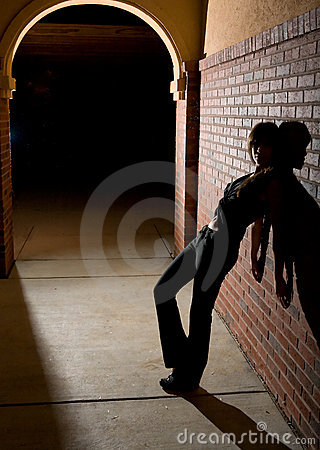 Young Woman Leaning Against Brick Wall at Night