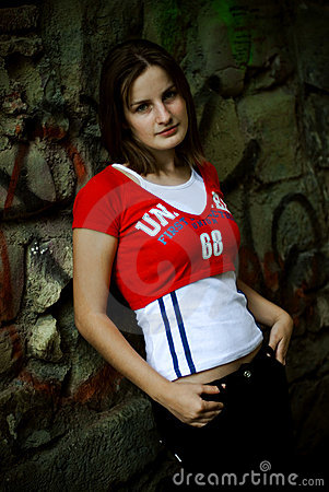 Young woman leaning on wall